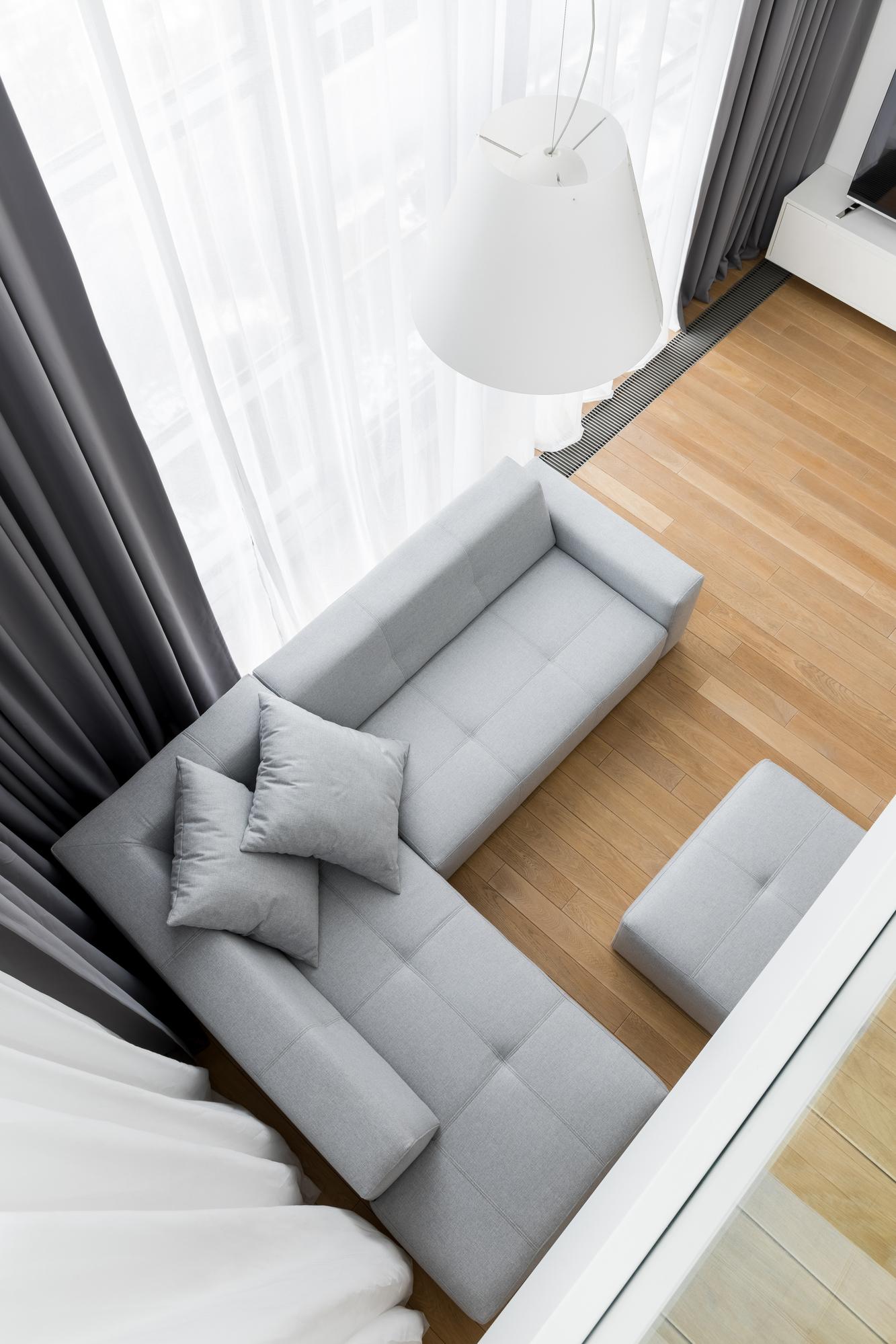 Detalle de sofá rinconero en salón estrecho y alargado
