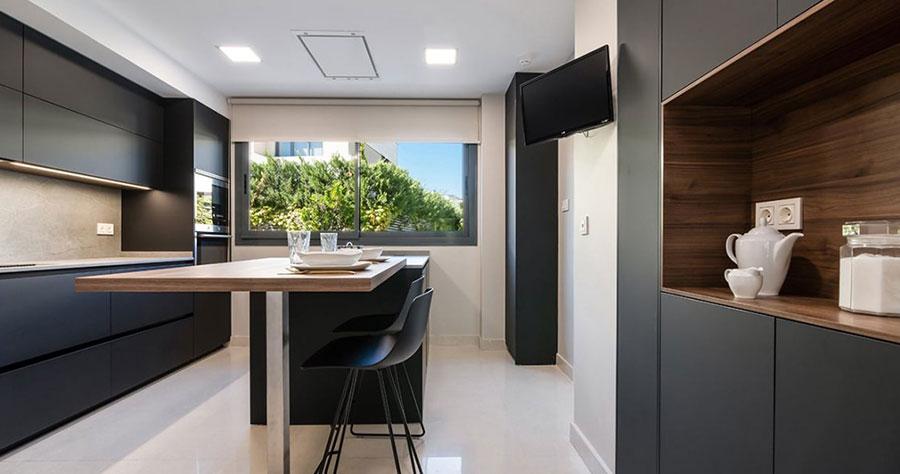 Diseño de cocina negra con isla con suelos y paredes blancas
